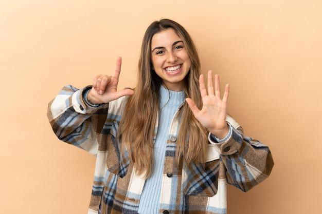 Jeune femme caucasienne isolée sur fond beige comptant sept avec les doigts