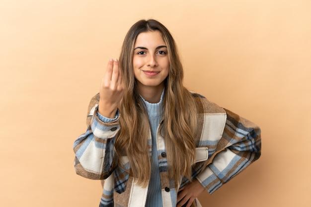 Jeune femme caucasienne isolée sur fond beige faisant un geste italien