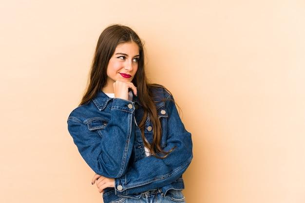 Jeune femme caucasienne isolée en fond beige à la recherche de côté avec une expression douteuse et sceptique.