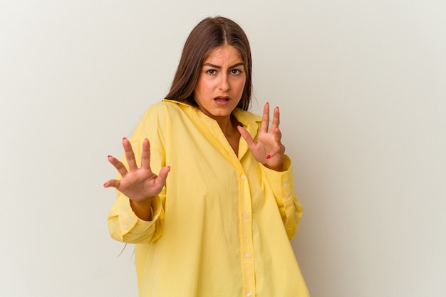 Jeune femme caucasienne isolée sur fond blanc couvrant les oreilles avec les mains en essayant de ne pas entendre un son trop fort.