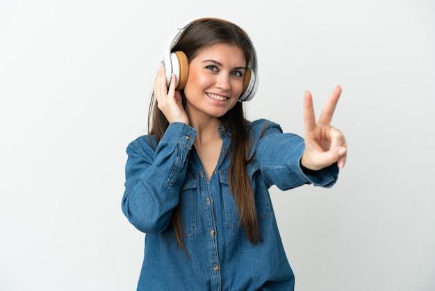 Jeune femme caucasienne isolée sur fond blanc, écouter de la musique et chanter