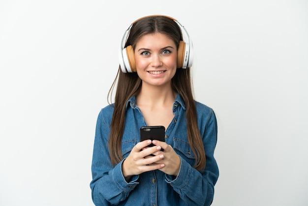 Jeune femme caucasienne isolée sur fond blanc, écouter de la musique avec un mobile et à l'avant