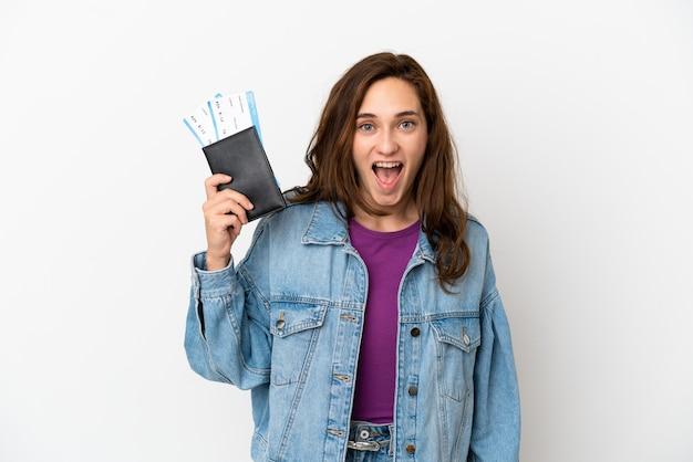 Jeune femme caucasienne isolée sur fond blanc heureuse en vacances avec passeport et billets d'avion