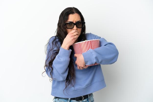 Jeune femme caucasienne isolée sur fond blanc avec des lunettes 3d et tenant un grand seau de pop-corn