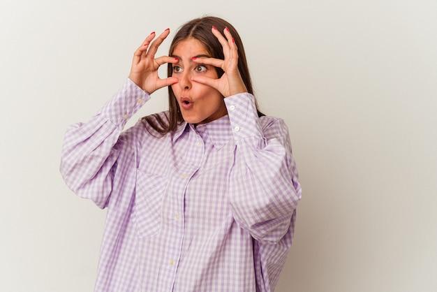 Jeune femme caucasienne isolée sur fond blanc malheureux à la recherche à huis clos avec une expression sarcastique.