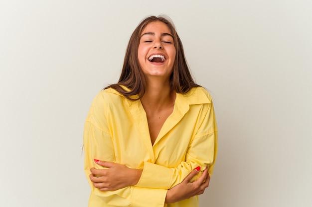 Jeune femme caucasienne isolée sur fond blanc rit joyeusement et s'amuse en gardant les mains sur le ventre.