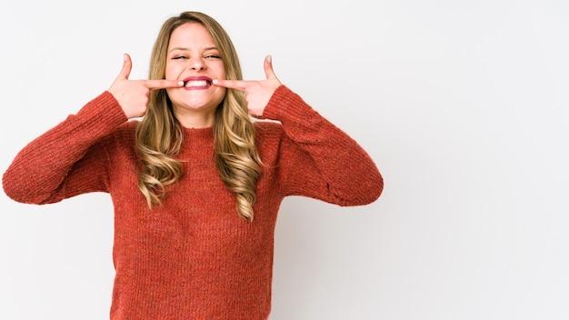 Jeune femme caucasienne isolée sur fond blanc sourit, pointant du doigt la bouche.