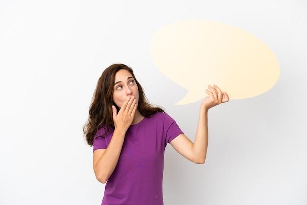 Jeune femme caucasienne isolée sur fond blanc tenant une bulle de dialogue vide avec une expression surprise
