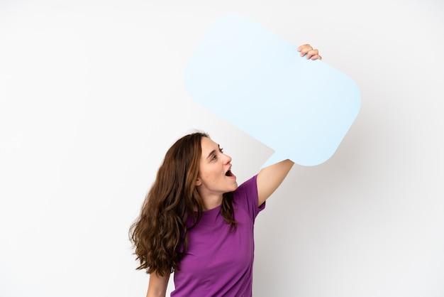 Jeune femme caucasienne isolée sur fond blanc tenant une bulle de dialogue vide