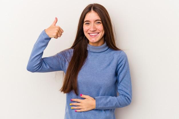 Jeune femme caucasienne isolée sur fond blanc touche le ventre, sourit doucement, mange et satisfait le concept.