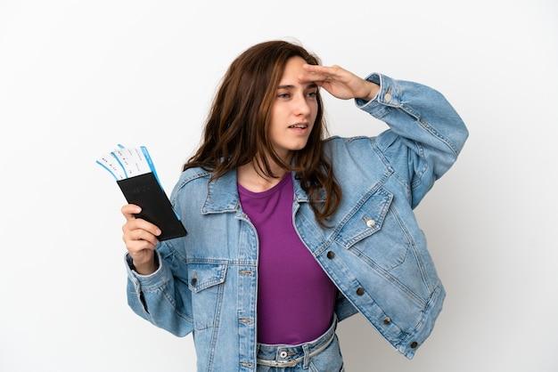 Jeune femme caucasienne isolée sur fond blanc en vacances avec passeport et billets d'avion tout en regardant quelque chose au loin