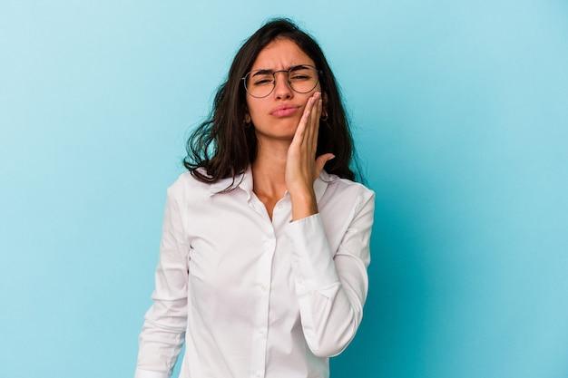 Jeune femme caucasienne isolée sur fond bleu ayant une forte douleur dentaire, une douleur molaire.