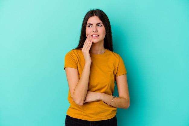 Jeune femme caucasienne isolée sur fond bleu ayant une forte douleur dentaire, mal molaire.