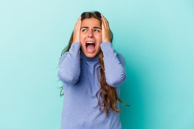 Jeune femme caucasienne isolée sur fond bleu couvrant les oreilles avec les mains essayant de ne pas entendre un son trop fort.