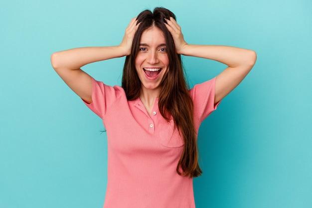 Jeune femme caucasienne isolée sur fond bleu criant, très excitée, passionnée, satisfaite de quelque chose.
