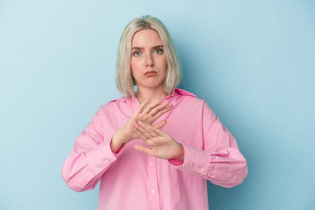 Jeune femme caucasienne isolée sur fond bleu debout avec la main tendue montrant un panneau d'arrêt, vous empêchant.