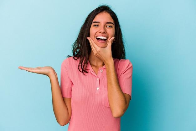 Jeune femme caucasienne isolée sur fond bleu détient un espace de copie sur une paume, garde la main sur la joue. émerveillé et ravi.