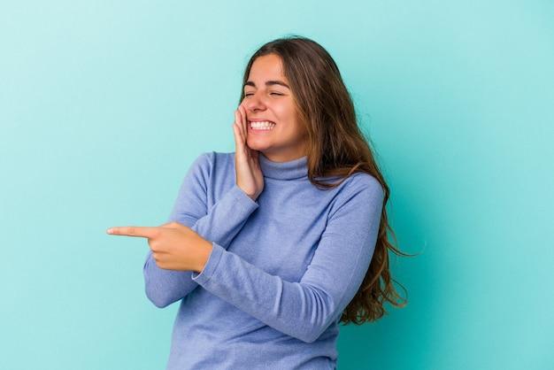 Jeune femme caucasienne isolée sur fond bleu disant un potin, pointant vers le côté rapportant quelque chose.