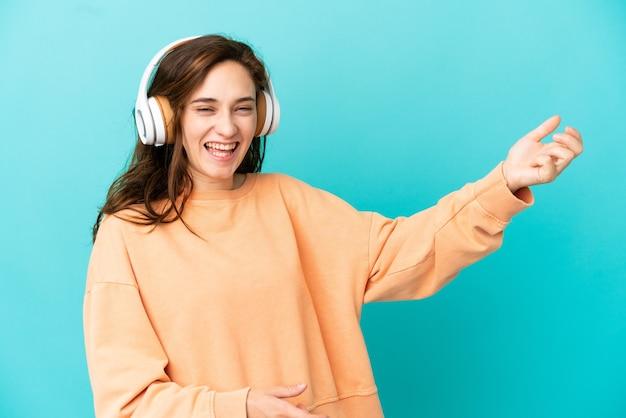 Jeune femme caucasienne isolée sur fond bleu écoutant de la musique et faisant un geste de guitare