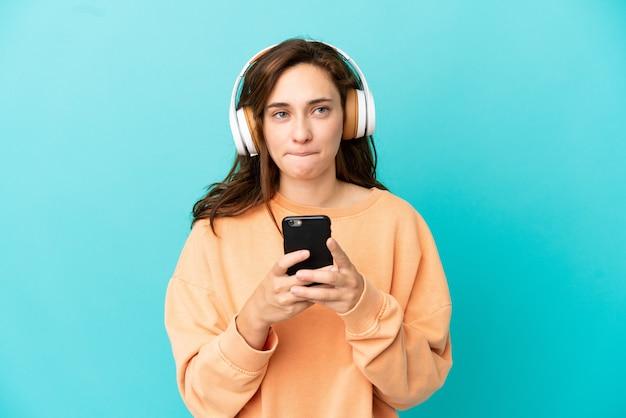 Jeune femme caucasienne isolée sur fond bleu, écoutant de la musique avec un mobile et pensant