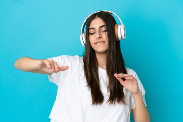 Jeune femme caucasienne isolée sur fond bleu, écouter de la musique et danser