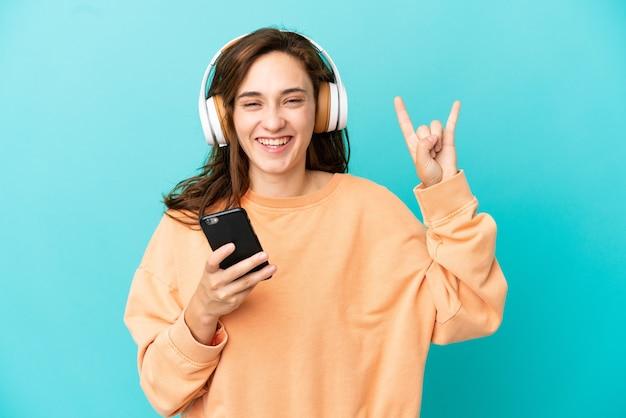 Jeune femme caucasienne isolée sur fond bleu, écouter de la musique avec un mobile faisant un geste rock