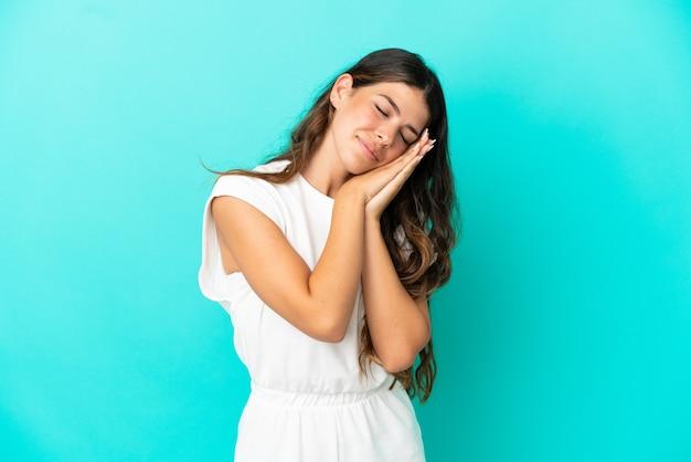 Jeune femme caucasienne isolée sur fond bleu faisant un geste de sommeil dans une expression adorable
