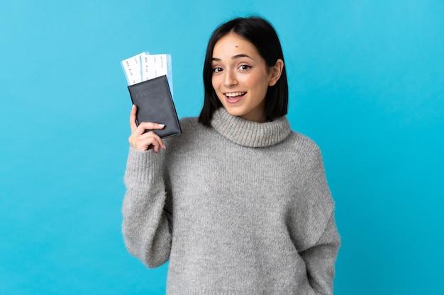 Jeune femme caucasienne isolée sur fond bleu heureux en vacances avec passeport et billets d'avion