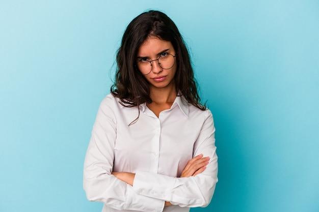 Jeune femme caucasienne isolée sur fond bleu malheureux à la recherche à huis clos avec une expression sarcastique.
