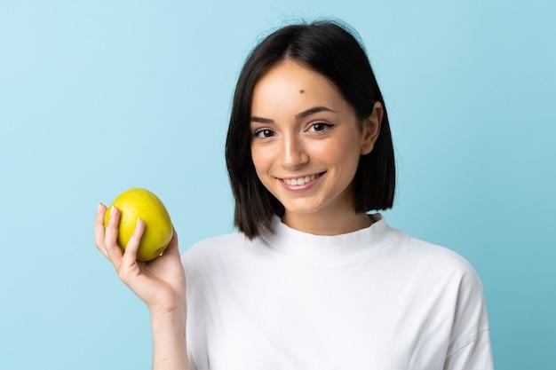 Jeune femme caucasienne isolée sur fond bleu avec une pomme