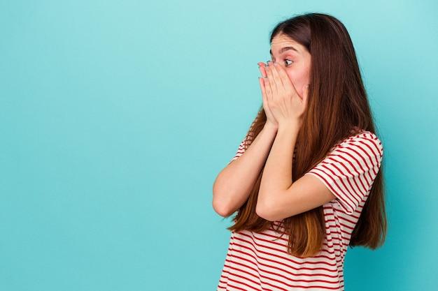 Jeune femme caucasienne isolée sur fond bleu réfléchie à la recherche d'un espace de copie couvrant la bouche avec la main.