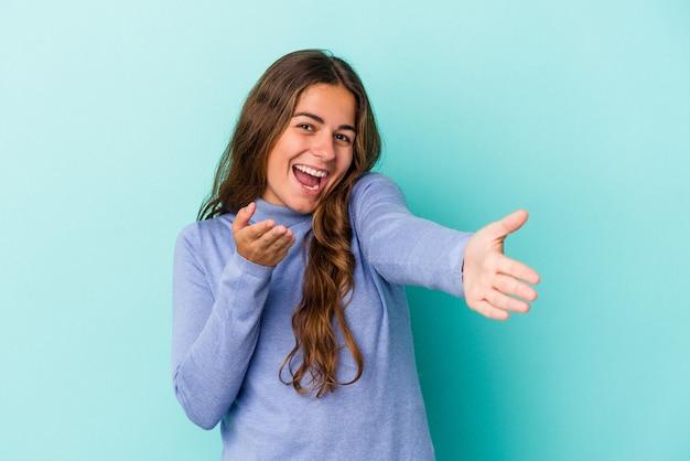 Jeune femme caucasienne isolée sur fond bleu se sent confiante en donnant un câlin à la caméra.