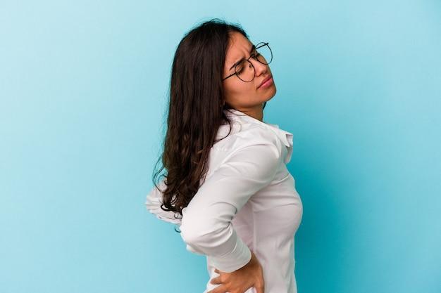 Jeune femme caucasienne isolée sur fond bleu souffrant d'un mal de dos.