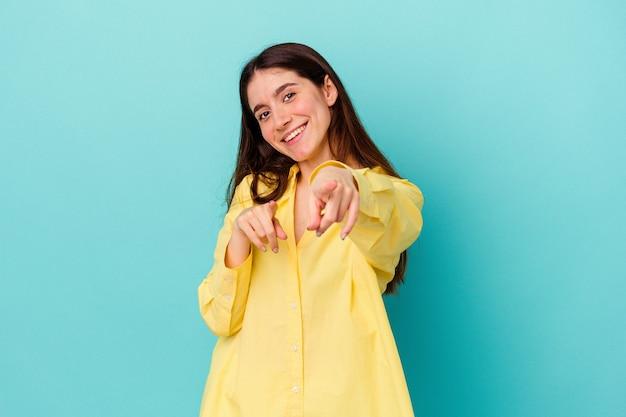 Jeune femme caucasienne isolée sur fond bleu, sourires joyeux pointant vers l'avant.