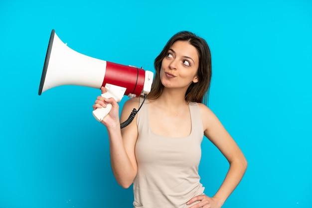Jeune femme caucasienne isolée sur fond bleu tenant un mégaphone et pensant