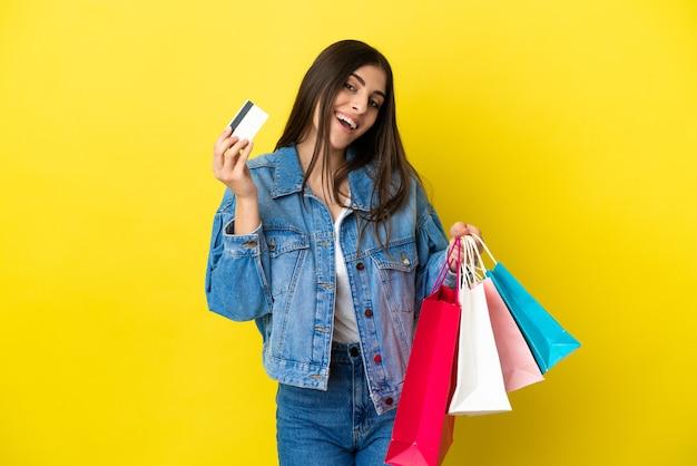 Jeune femme caucasienne isolée sur fond bleu tenant des sacs à provisions et une carte de crédit