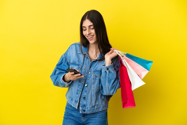 Jeune femme caucasienne isolée sur fond bleu tenant des sacs à provisions et écrivant un message avec son téléphone portable à un ami