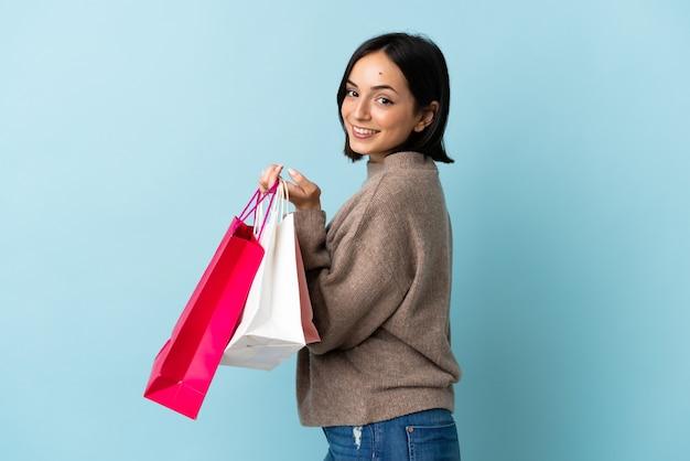 Jeune femme caucasienne isolée sur fond bleu tenant des sacs à provisions et souriant