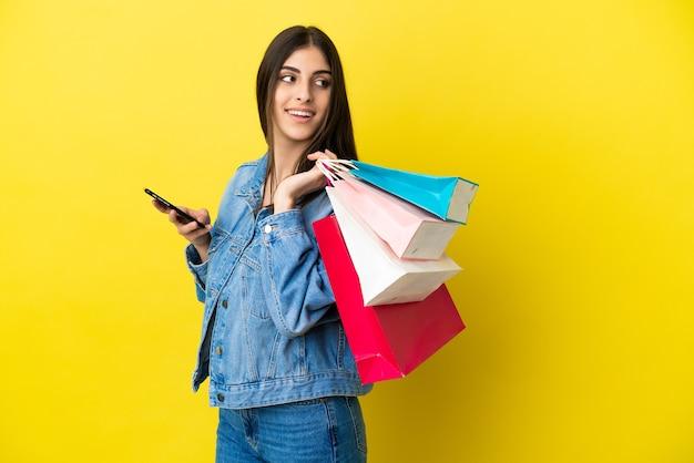 Jeune femme caucasienne isolée sur fond bleu tenant des sacs à provisions et un téléphone mobile