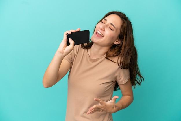 Jeune femme caucasienne isolée sur fond bleu utilisant un téléphone portable et chantant
