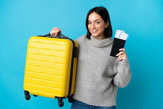 Jeune femme caucasienne isolée sur fond bleu en vacances avec valise et passeport