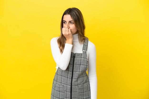 Jeune femme caucasienne isolée sur fond jaune ayant des doutes