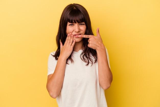 Jeune femme caucasienne isolée sur fond jaune ayant une forte douleur dentaire, une douleur molaire.
