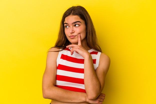 Jeune femme caucasienne isolée sur fond jaune contemplant, planifiant une stratégie, réfléchissant à la manière d'une entreprise.