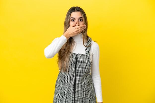 Jeune femme caucasienne isolée sur fond jaune couvrant la bouche avec la main