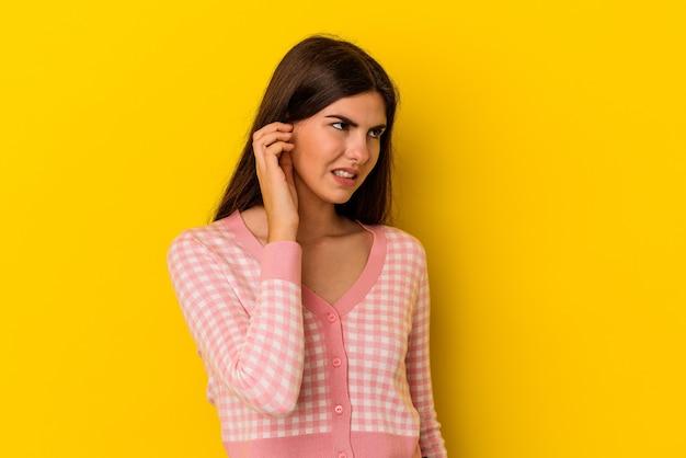 Jeune femme caucasienne isolée sur fond jaune couvrant les oreilles avec les mains.