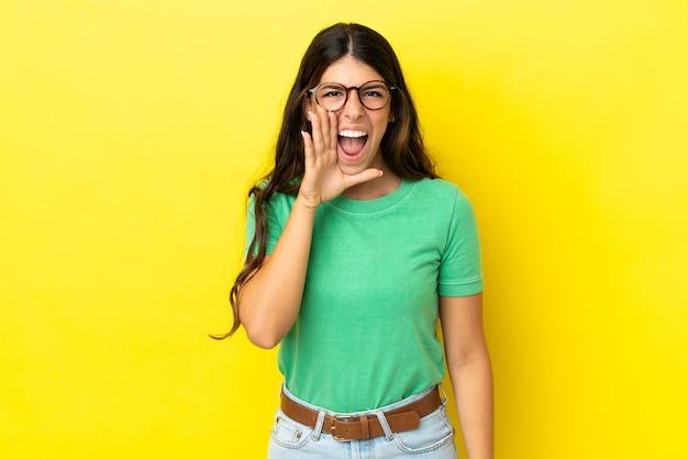 Jeune femme caucasienne isolée sur fond jaune criant avec la bouche grande ouverte