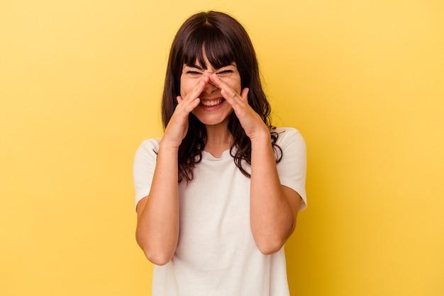 Jeune femme caucasienne isolée sur fond jaune disant un potin, pointant vers le côté rapportant quelque chose.