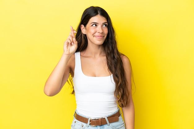Jeune femme caucasienne isolée sur fond jaune avec les doigts croisés et souhaitant le meilleur