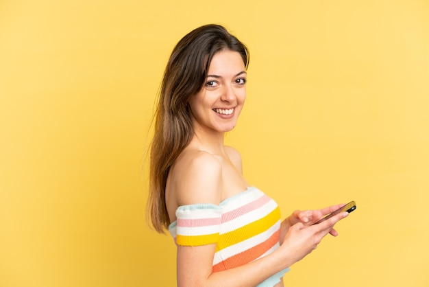 Jeune femme caucasienne isolée sur fond jaune envoyant un message ou un e-mail avec le mobile